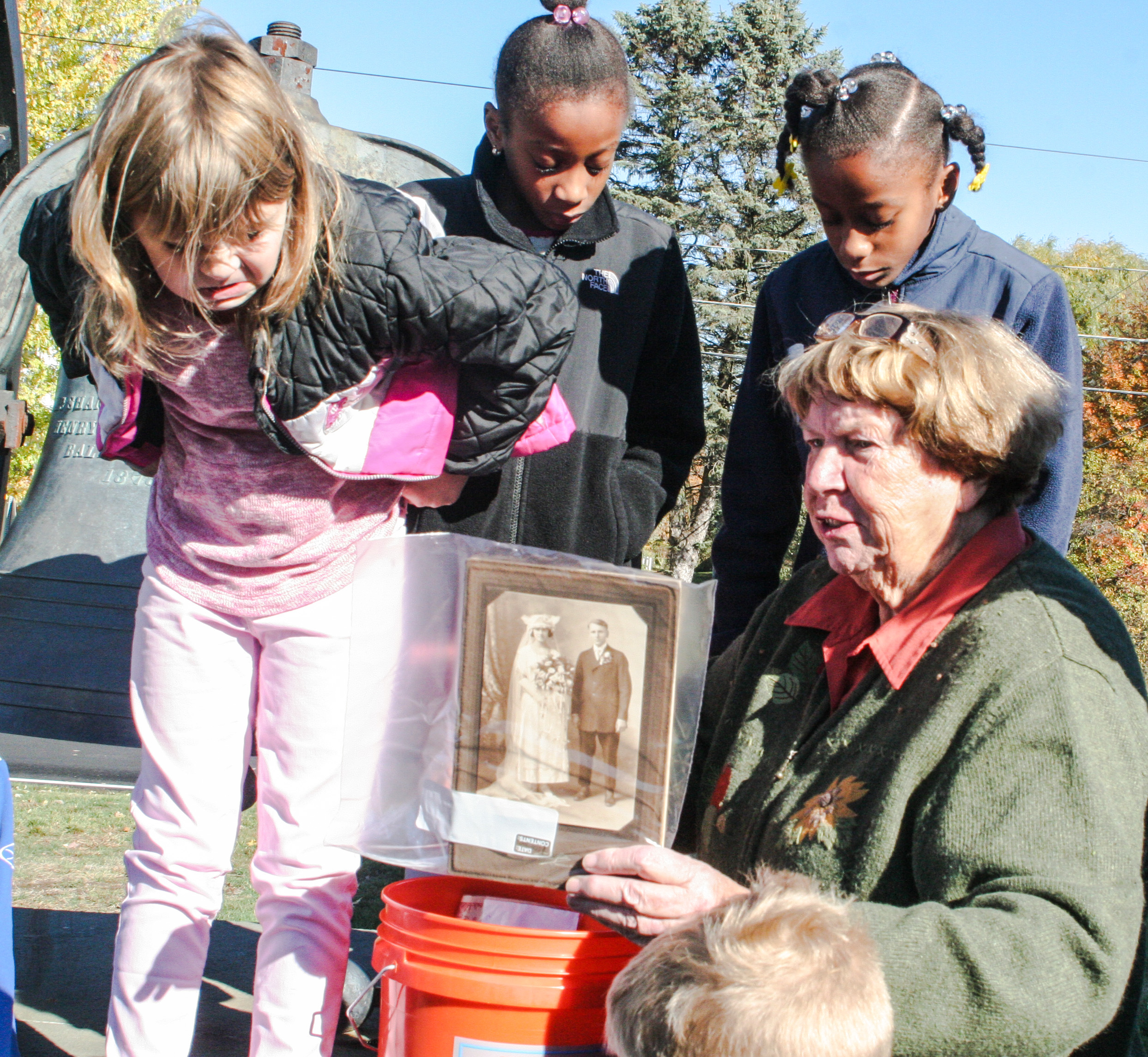 Chairperson Carol Griffin explaining time capsule with children looking on